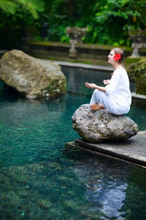 Young beautiful woman meditating near water pond