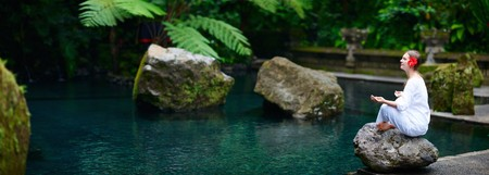 meditating woman: Panoramic photo of young beautiful woman meditating near water pond Stock Photo