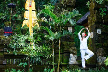 Young beautiful woman making yoga exercise near beautiful Bali temple Stock Photo - 8061040