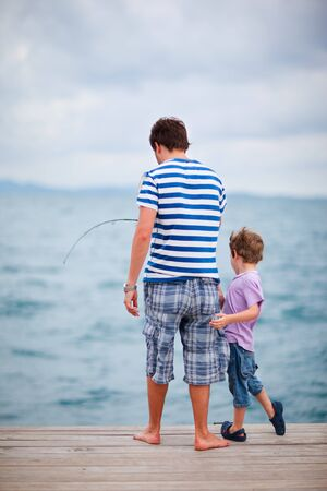 Young father and his son fishing together from wooden jetty photo
