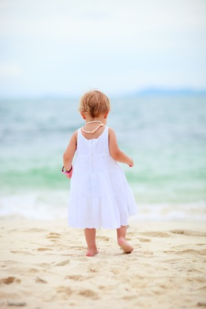 standing water: Back view of baby girl at tropical beach Stock Photo