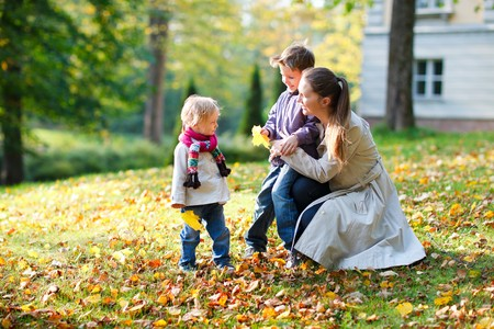 autumn family: Young mother with here two kids at autumn park