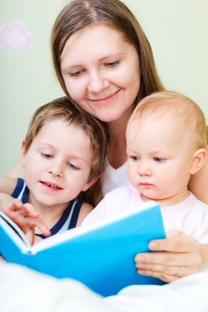 Young mother with her two kids reading book in bed Stock Photo - 8061144