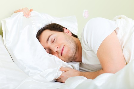 Young handsome man sleeping in bed photo