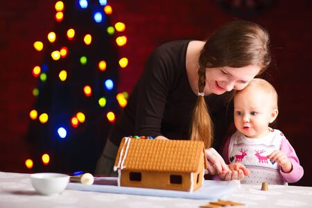 Young mother and her adorable baby daughter decorating gingerbread house photo