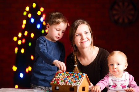 Family decorating gingerbread house on Christmas eve photo