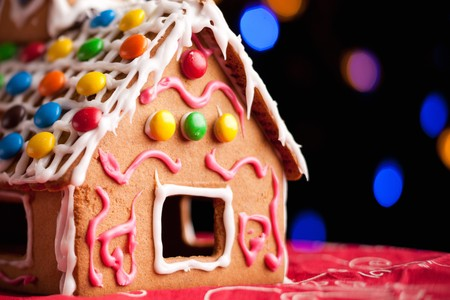 Closeup of gingerbread house decorated with colorful candies over Christmas tree lights background photo