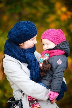 Portrait of young beautiful woman and her adorable little daughter outdoors photo