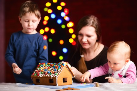 Family making gingerbread house photo