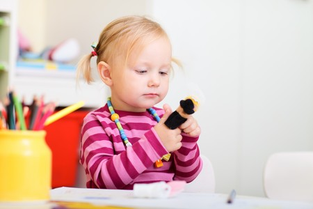 Toddler girl playing with finger puppets photo