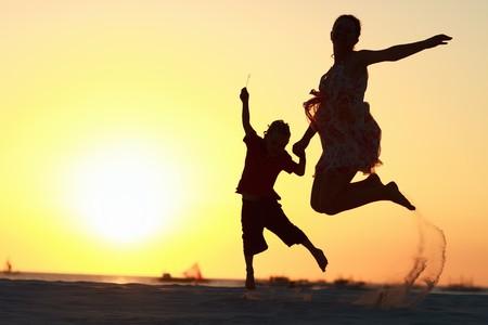 springende mensen: Moeder en zoon silhouetten springen op het strand bij zons ondergang