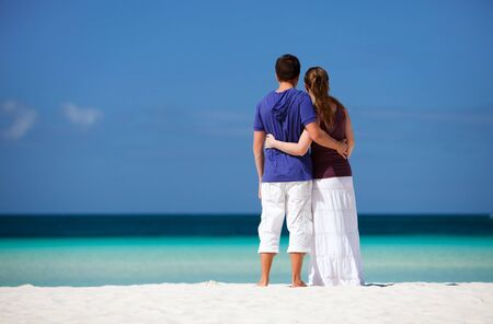 Back view of young happy couple on white sand beach photo