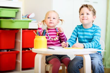 Happy brother and sister sitting together drawing with pencils Stock Photo - 8221964