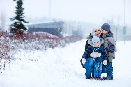 ropa de invierno: Madre joven con dos ni�os al aire libre en invierno hermoso d�a