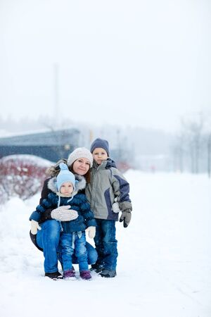 Young mother with two kids outdoors on beautiful winter day photo