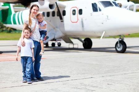 persona viajando: Joven madre con sus dos hijos permanente de peque�o avi�n