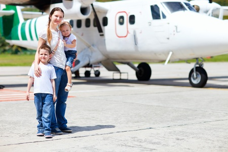 Young mother with her two kids standing in front of small airplane Stock Photo - 8592782