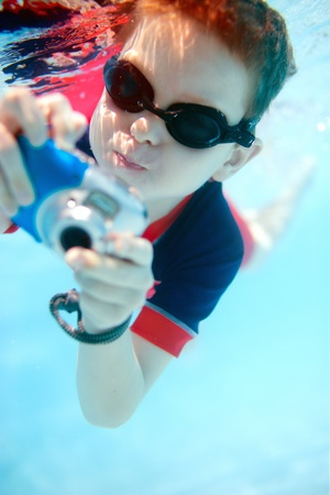 Cute little boy swimming underwater with compact camera photo