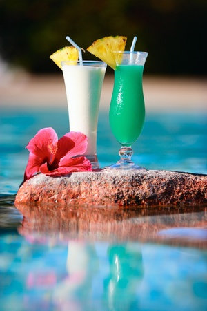Closeup of two tropical cocktails near water photo