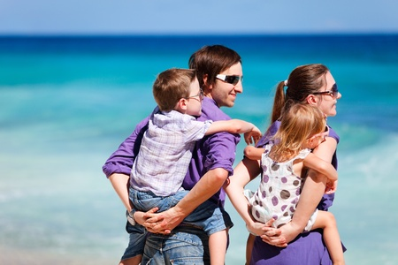 Portrait of young parents holding their kids on back and looking to ocean photo