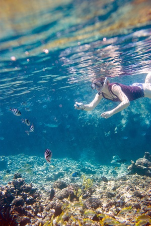 Woman snorkeling and making photos of underwater life photo
