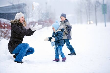 Mother and two kids having fun outdoors on beautiful winter day photo