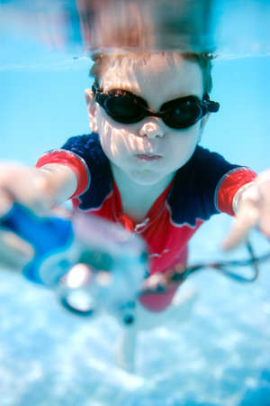 Cute 6 years old boy swimming underwater and making photos photo