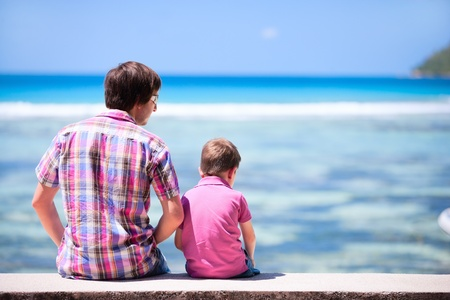 Back view of father and son sitting together and looking to ocean? Stock Photo - 8610858