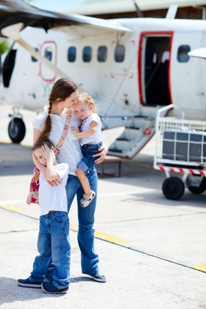 Young mother with her two kids standing in front of small airplane photo