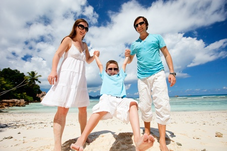 Happy young family having fun on tropical beach photo