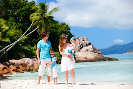 Portrait of happy young family with two kids on tropical vacation photo