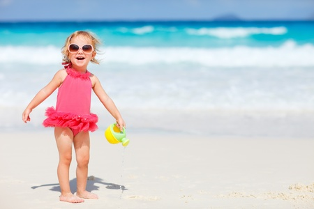 kids playing water: Adorable toddler girl playing with beach toys on white sand beach Stock Photo