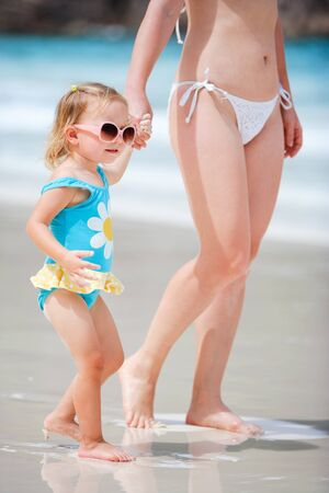 Closeup of mother and her adorable little daughter walking at beach photo