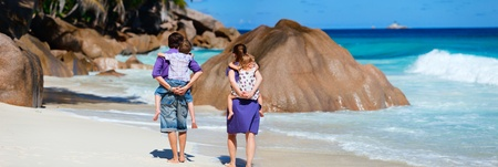 Panoramic photo of family with two kids walking along tropical beach photo