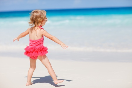 Back view of playful toddler girl on white sand beach photo