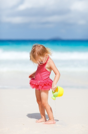 kids playing beach: Adorable toddler girl playing with beach toys on white sand beach Stock Photo