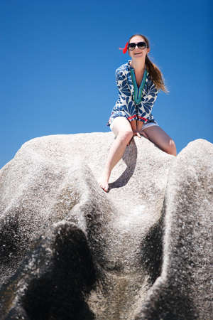 d argent: Young beautiful woman at Anse Source d Argent beach in Seychelles sitting on granite rock