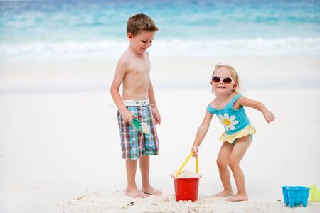 Brother and sister playing together on send beach photo