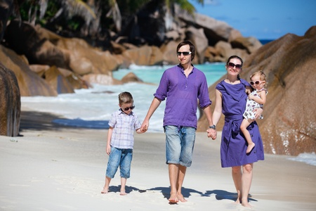 Portrait of happy young family with two kids walking along tropical beach photo