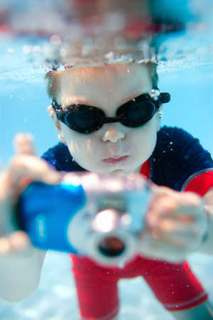 undersea: Cute little boy swimming underwater and photographing