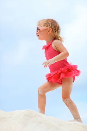 Cute little girl walking at tropical beach. photo