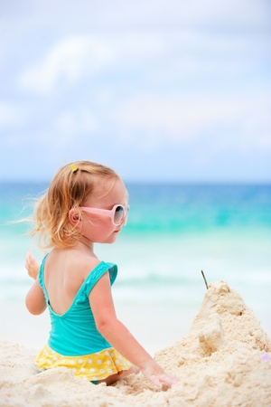 Adorable toddler girl playing with sand on tropical beach photo