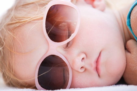 Portrait of adorable toddler girl sleeping at beach photo