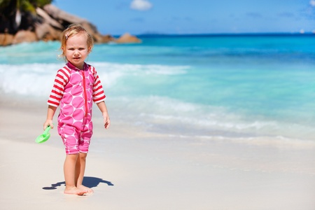 Adorable toddler girl playing with beach toy at white sand beach photo