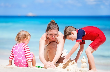Young mother and her two kids building sand castle at beach photo