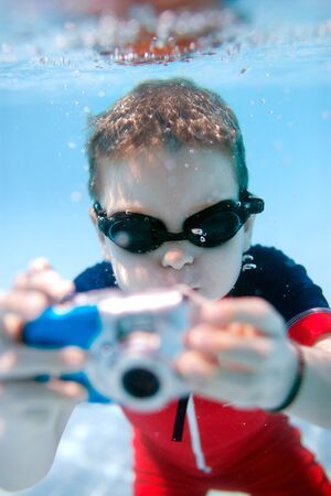 Cute little boy swimming underwater and photographing photo