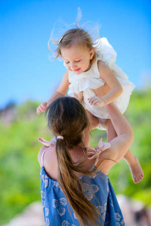 Mother and daughter having fun outdoors on summer day photo