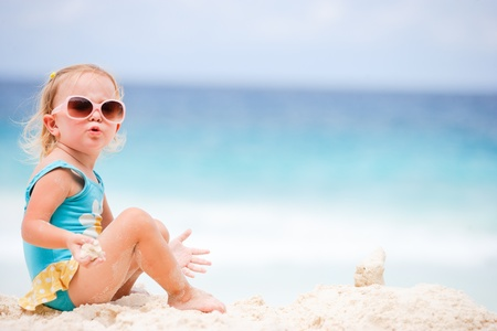 Adorable toddler girl at tropical beach playing with sand photo