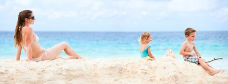 Panoramic photo of young mother and her two kids at beach photo