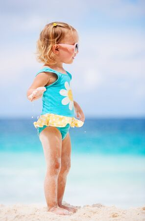 Adorable toddler girl in blue and yellow swimsuit standing at tropical beach photo